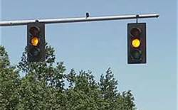 You see a flashing yellow traffic signal at an upcoming intersection. The flashing yellow light means: