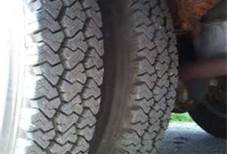 You find an overheated tire during an enroute inspection. If you are hauling hazardous materials, you must: