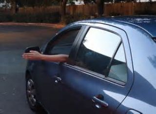 If a driver extends his/her left arm horizontally out of an open window while driving on a road, this indicates that the driver is going to: