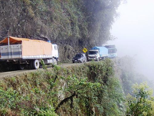 When two vehicles meet on a steep mountain road where neither can pass, which vehicle has the right-of-way?